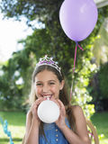 Happy Girl In Tiara Blowing Balloons Outdoors
