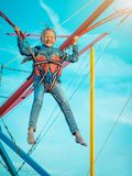 Happy girl tied with belts swinging the attraction closed from fear through the eyes. The child in the amusement Park Stock Photography