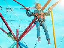 The girl screams in fear off the attraction tied belts. Happy girl tied with belts swinging the attraction closed from fear through the eyes. The child in the Stock Photography