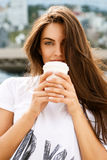 Happy girl with to go cup. Happy beautiful female cute brunette lady with long healthy hair in front of business sport building hold with two hands paper cup Stock Photos