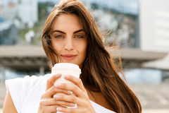 Happy girl with to go cup. Happy beautiful woman cute brunette girl with long healthy hair in front of business sport building hold with two hands paper cup with Stock Photos