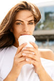 Happy girl with to go cup. Portrait of happy beautiful brunette girl with long healthy hair in front of business sport building hold with two hands paper cup Royalty Free Stock Photo