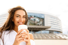 Happy girl with to go cup. Portrait of happy cute girl with long healthy sexy hair in front of business sport building hold with two hands paper cup with hot Stock Image