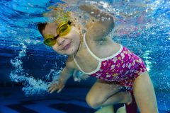 Happy girl toddler swimming underwater. Happy cute smiling girl toddler swimming underwater producing lots of bubbles Royalty Free Stock Images