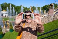Happy girl tourist shooting selfie in Peterhof in Saint Petersbu Royalty Free Stock Photos