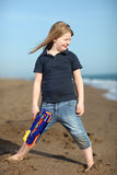 Happy girl with toy gun on the beach Stock Photo