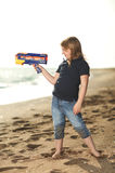 Happy girl with toy gun on the beach Royalty Free Stock Photo