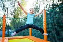 Happy Girl on Trampoline. Happy caucasian girl jumping high on a trampoline on a sunny day outdoors Royalty Free Stock Photography