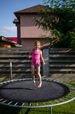 Happy girl on a trampoline Stock Photos