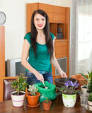 Happy girl transplanting potted flowers. At home stock images