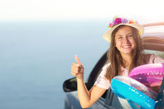 Happy girl  travel by car to the sea. Child having fun, showing Stock Image