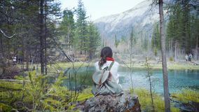 Happy girl traveler sits on the rock, looks at a mountain crater lake. Dressed in a jeans hiking jacket and hiking stock video
