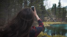 Happy girl traveler sits on the rock, makes a picture on the smartphone mountain crater lake. Dressed in a jeans hiking. Jacket and hiking backpack. Travel stock footage