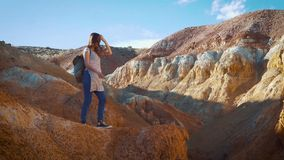 Happy girl traveler walks the red mountains. The mountains are like mars, red clay. Travel alone, finding yourself. Happy girl traveler walks the red mountains stock video