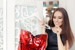Happy Girl Trying on Red Party Dress in Dressing Room Stock Image