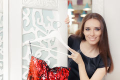 Happy Girl Trying on Red Party Dress in Dressing Room Royalty Free Stock Images