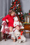 Happy girl with two puppies Golden Retriever on a background of Christmas tree. Happy girl 6 years old with gray-green eyes,brunette hair braided in two pigtails Royalty Free Stock Photography