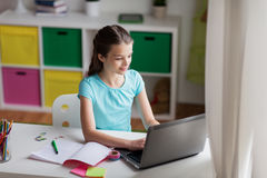 Happy girl typing on laptop at home Stock Photography