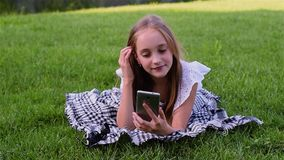 Happy girl typing sms by phone lies on grass in the park stock video