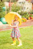 Happy girl with an umbrella in rubber boots after a rain on a summer day in the park Royalty Free Stock Photo