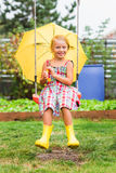 Happy girl with an umbrella in rubber boots after a rain on a summer day in a park on a swing Stock Photography