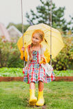 Happy girl with an umbrella in rubber boots after a rain on a summer day in a park on a swing Royalty Free Stock Photo