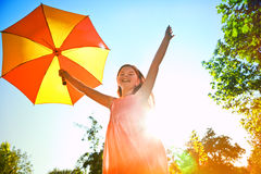 Happy girl with umbrella in sun. Happy redhead girl with umbrella in summer sun. Freedom, summer, childhood concept royalty free stock photography