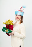 Happy girl in an unusual Christmas hat with gift boxes Stock Images