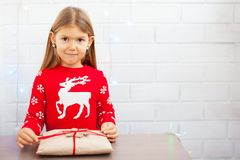 Happy girl unwraping a Christmas gift stock photography