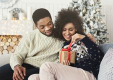 Happy girl unwrapping christmas present from her boyfriend. Happy smiling girl unwrapping new year present from her boyfriend near christmas tree stock images