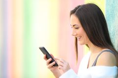 Happy girl uses a smart phone in a colorful street royalty free stock image