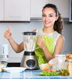 Happy girl using blender and grinding ingredients Stock Images