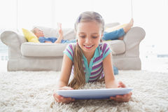 Happy girl using digital tablet on rug at home Stock Photo