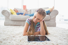Happy girl using digital tablet on rug in living room Royalty Free Stock Photo
