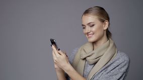 Happy girl using mobile phone. Isolated over gray background stock footage