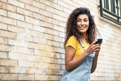 Happy girl using smart phone on brick wall. Smiling woman with curly hairstyle in casual clothes in urban background royalty free stock image
