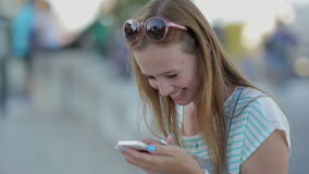 Happy girl using a smart phone in a city stock footage