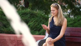 Happy girl using a smartphone in a city park sitting on a bench next to the fountain.  stock video footage