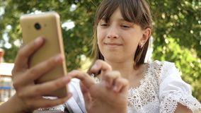Happy girl using smartphone scrolls through pages in the online store in the park on the bench. Young millennial woman stock video