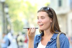 Girl using voice recognition of the phone in the street. Happy girl using voice recognition of the smart phone in the street Stock Photos