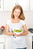 Happy girl with a vegetable salad in the kitchen Royalty Free Stock Photo