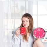 Happy girl  wake up with alarm clock and  coffee Royalty Free Stock Photography