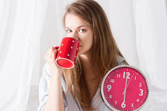Happy girl wake up with alarm clock and coffee. Happy girl wake up , thumbs up with alarm clock and coffee cup 6 a.m stock photos