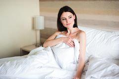 Happy girl waking up stretching arms on the bed in the morning. stock photo