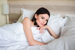 Happy girl waking up stretching arms on the bed in the morning. stock photography