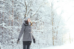 Happy girl walking in a beautiful winter forest. Happy girl walking in beautiful winter forest. Christmas concept Royalty Free Stock Images
