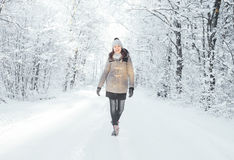 Happy girl walking in a beautiful winter forest Stock Images