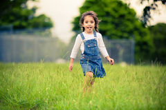 Happy girl walking in a green meadow Stock Photo