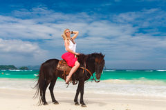 Happy girl walking with horse on a tropical beach Royalty Free Stock Image