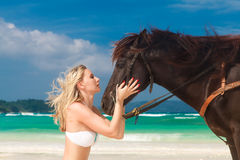 Happy girl walking with horse on a tropical beach Royalty Free Stock Photos